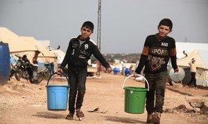 Deux enfants portent de l'eau dans un camp de déplacés à Idlib, en Syrie (photo d'archives).