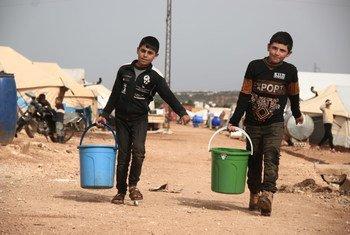 Crianças levam baldes com água em campo de deslocados na Síria