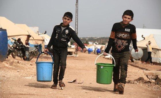 Two children cod  drinking h2o  successful  a campy  for displaced radical   successful  Idlib, Syria.