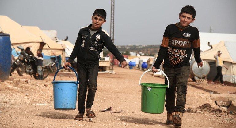 طفلان يجمعان مياه الشرب في مخيم للنازحين في إدلب بسوريا.