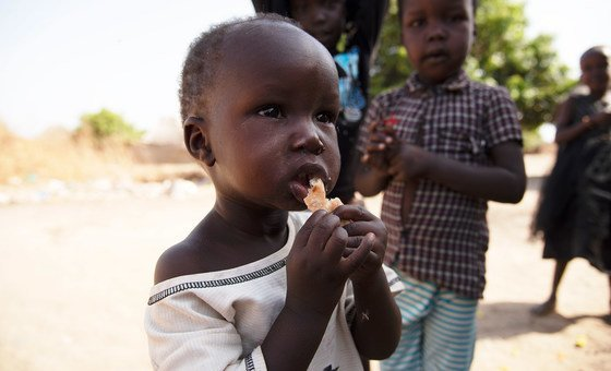 A 17-month-old boy who was treated for acute malnutrition at a UNICEF-supported nutrition programme, eats breakfast outside his home in Aweil, South Sudan.