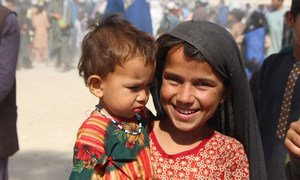 A seven-year-old girl holds her younger sister in an IDP camp in Kandahar, southwestern Afghanistan.