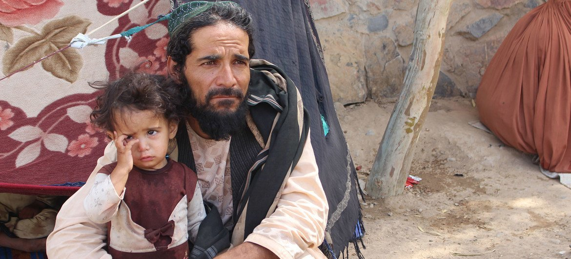 A father and his daughter in a camp for displaced people, two of 18 million people in Afghanistan who are in need of humanitarian aid, .