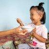 किर्गिज़स्तान में एक माँ अपनी तीन वर्ष की बेटी को खाना खिला रही है.