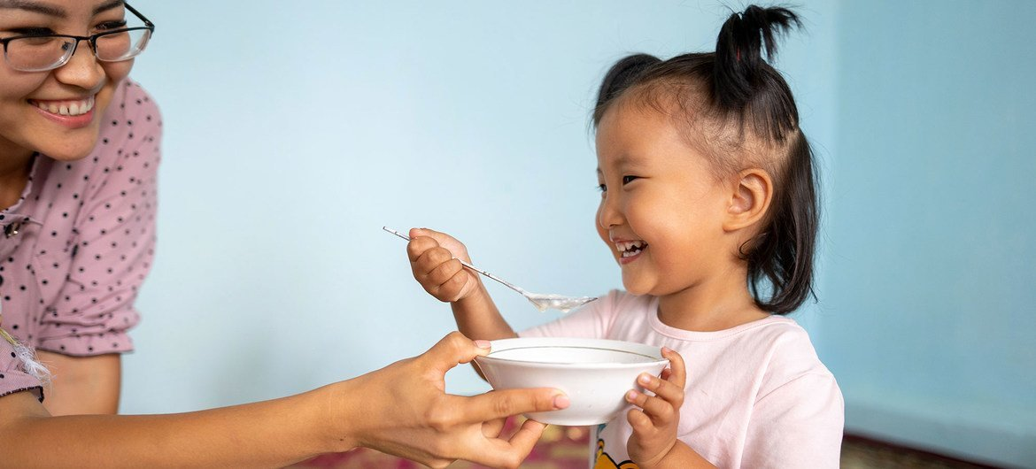 A mother helps her three-year-old girl eat porridge at home in Kyrgyzstan.
