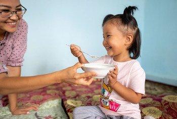 吉尔吉斯斯坦的一位母亲在家里帮助她三岁的女儿喝粥。