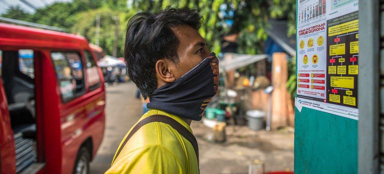 مواطن أندونيسي يقرأ معلومات الوقاية من كوفيد -19 في جاكرتا.