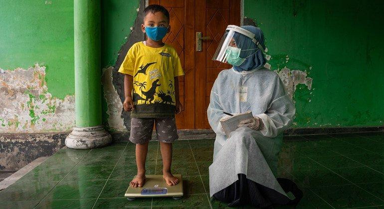 इंडोनेशिया के मध्य जावा प्राँत के सामुदायिक स्वास्थ्य केंद्र में एक बच्चे का वज़न लिया जा रहा है.