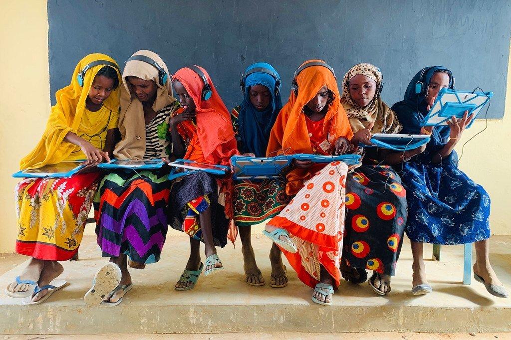 苏丹卡萨拉,几名女童正通过平板电脑和耳机进行远程学习。