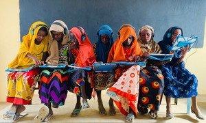 सूडान के एक गाँव में एक कक्षा में लड़कियाँ टैबलेट पर शिक्षा ले रही हैं.