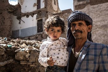 也门萨那,一位父亲抱着孩子站在被摧毁的房屋前。