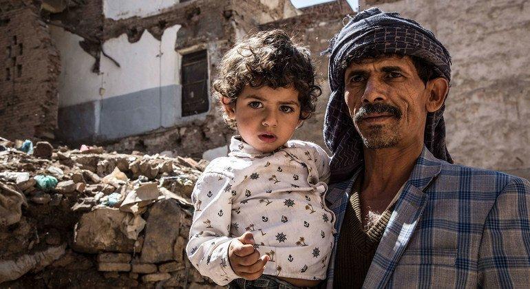 यमन में एक पिता अपनी बेटी को गोद में लेकर एक नष्ट हुई इमारत के सामने खड़ा है.