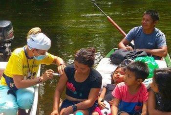 Мать из семьи коренного населения Бразилии получает прививку от COVID-19.