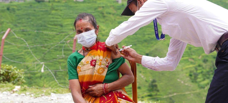 Une femme est vaccinée contre le COVID-19 dans un poste de santé du district reculé de Darchula, au Népal.