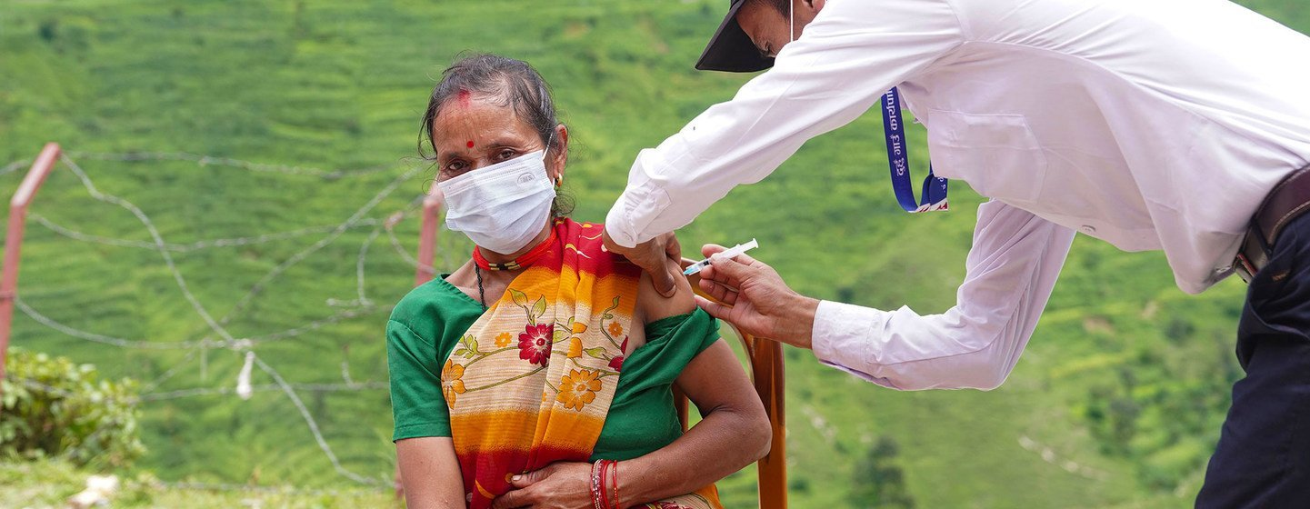 A woman is vaccinated against COVID-19 at a health post in Nepal's remote Darchula District.