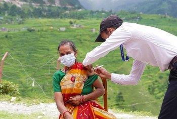 Vacunación de una mujer contra la COVID-19 en un puesto de salud del remoto distrito de Darchula, en Nepal.