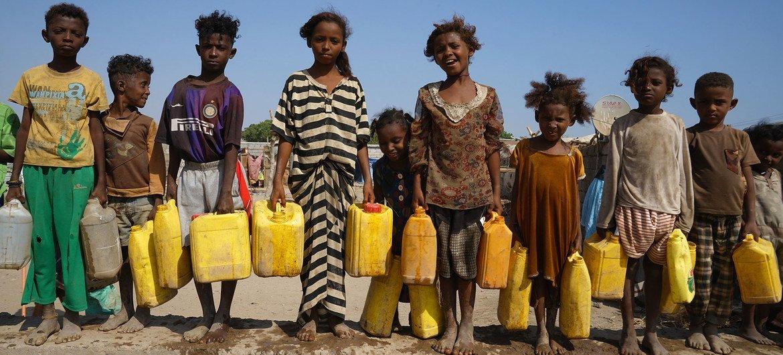 यमन के अदन में विस्थापित बच्चों को अपने शिविर में जल के लिये कण्टेनर का इसतेमाल करना पड़ता है.