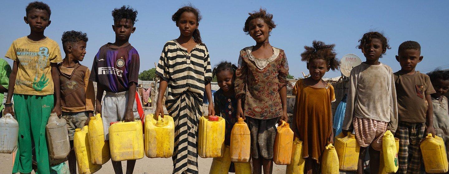 Niños yemeníes desplazados en un asentamiento de Adén sostienen contenedores durante la distribución de agua dos veces al día.
