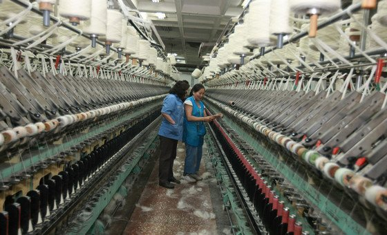 Two women check industrial looms in a rug factory in Mongolia. International rules and practices have locked developing countries into pre-pandemic responses
