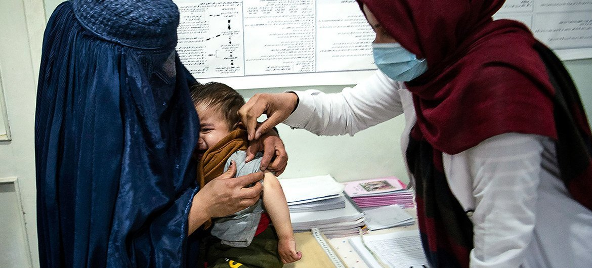 A  health worker cares for a young boy in Parwan Province, Afghanistan in November 2020.