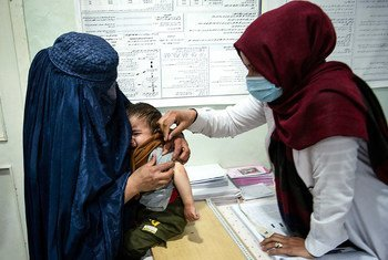 Un agent de santé s'occupe d'un jeune garçon dans la province de Parwan, en Afghanistan, en novembre 2020.