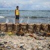 A boy stands on a seawall that protects his family home from the rising seas in Majuro Atoll in the Marshall Islands.
