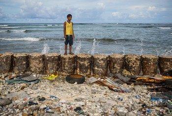 Un niño en el dique que protege el hogar familiar de las mareas crecientes del atolón de Majuro en las Islas Marshall.