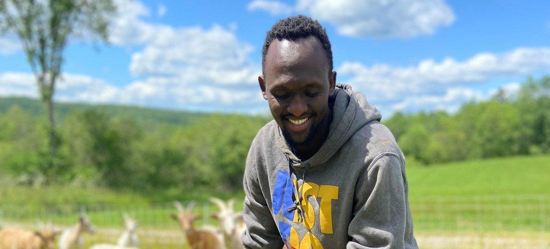 现在为缅因州刘易斯顿索马里班图社区协会农民成员的一名前难民正在照看一群山羊。