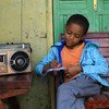 A young boy in Ethiopia attends class at home, taking lessons via the radio, which are being broadcast across the country.