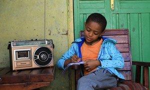 इथियोपिया में एक बच्चा घर बैठकर रेडियो कार्यक्रम के सहारे अपनी पढ़ाई कर रहा है क्योंकि कोविड-19 के कारण स्कूल बंद हैं.