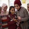 شابات سوريات يستخدمن الهواتف الذكية خارج مختبر تكنولوجي في دمياط بمصر.