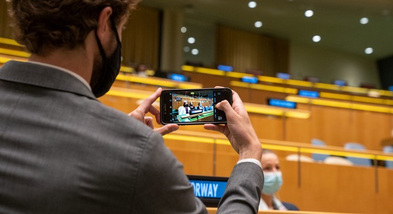 As the prime Minister of Norway, addresses the general debate, a delegate takes a photo of the country's position in the General Assembly hall.