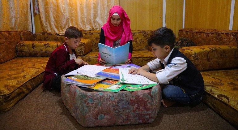En un campo de refugiados en Jordania, una joven siria ayuda a su hermano menor y a un vecino a estudiar durante la pandeia.