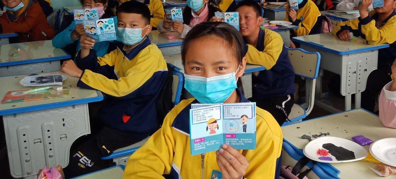 Alunos seguram folhetos com informações de saúde sobre Covid-19 em sala de aula na província de Qinghai, China.