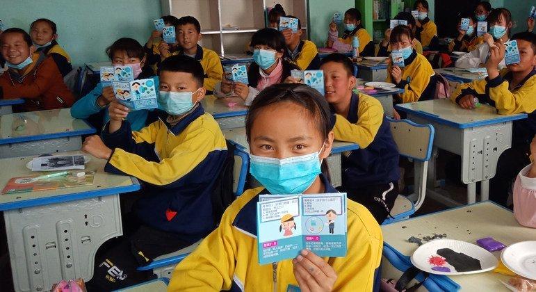 Estudiantes de la provincia de Qinghai en China reciben folletos para protegerse del COVID-19