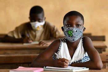 Wanafunzi nchini Cote d'Ivoire wanavaa barakoa wakihudhuria shule baada ya kufunguliwa.