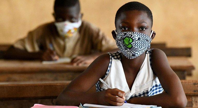 Niños en Côte d'Ivoire utilizan mascarillas en la escuela.