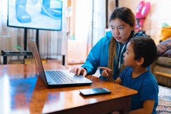 متطوعة في اليونيسف تراجع الدروس في المنزل في أوش بقيرغيزستان مع ابن أخيها كجزء من استجابة اليونيسف لجائحة كوفيد-19.