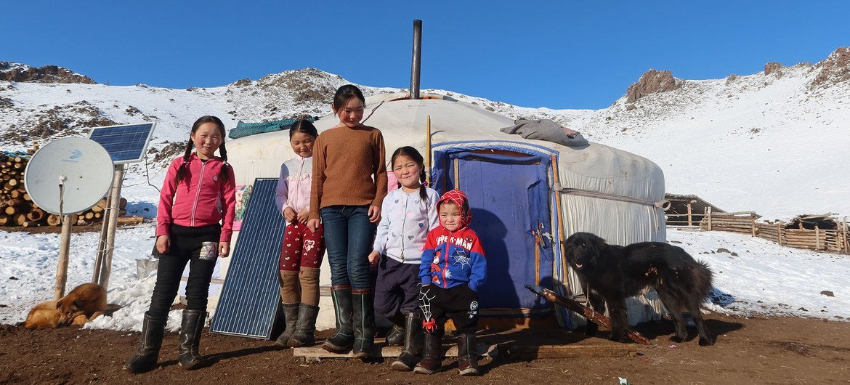 Children from a herding family in rural Mongolia line up outside their yurt.