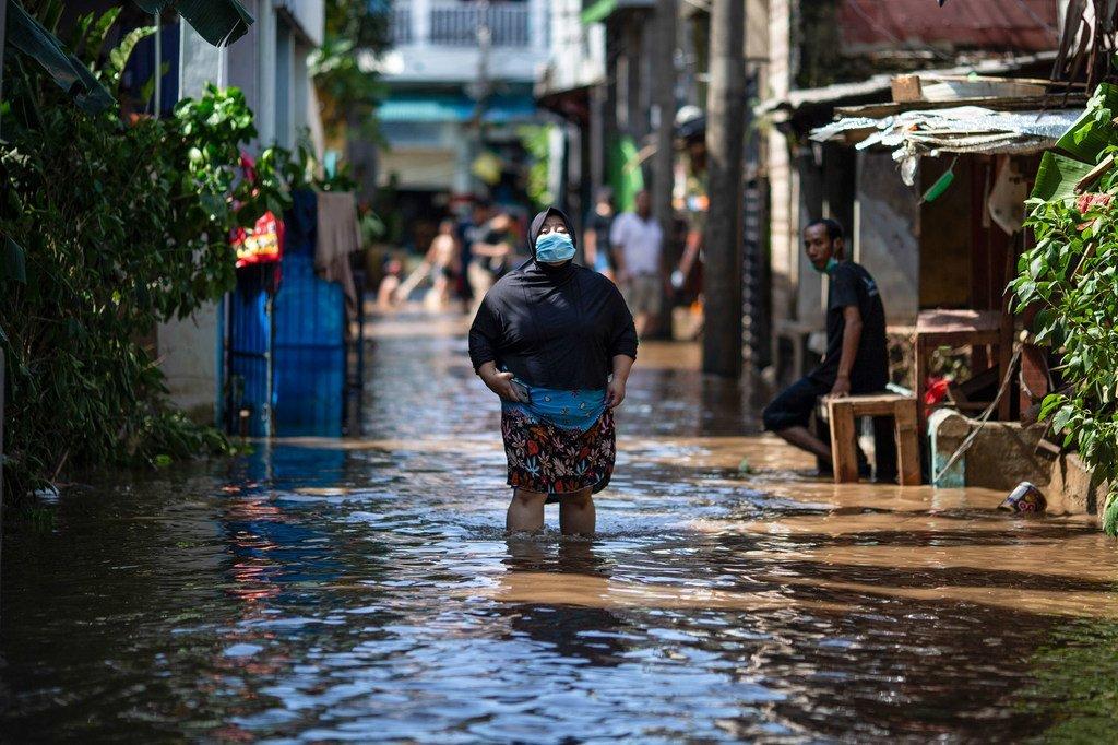 Una mujer camina a través de un área afectada por las inundaciones en el este de Jakarta, en Indonesia.