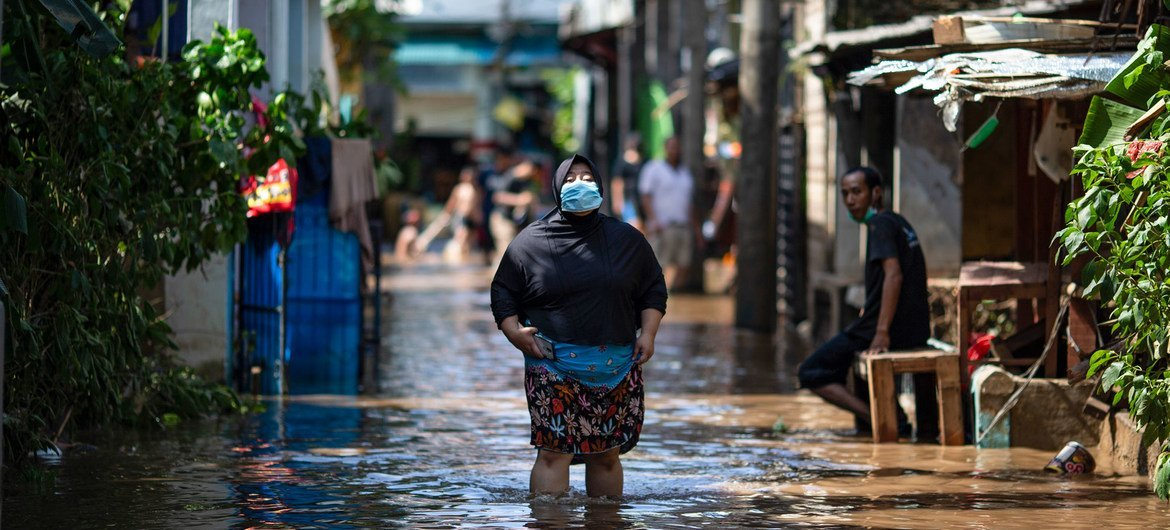 A pistillate   walks done  h2o  successful  an country  affected by flooding successful  East Jakarta, Indonesia.