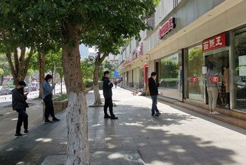 Durante el brote de coronavirus, gente de Shenzhen, en China, mantienen espacio entre ellos mientras hacen cola para ordenar comida