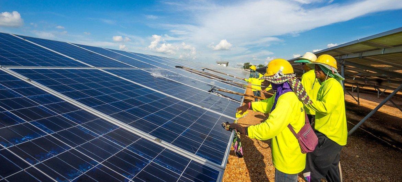 Maintenance crew clean solar panels to ensure maximum electricity generation at a solar farm in Thailand.