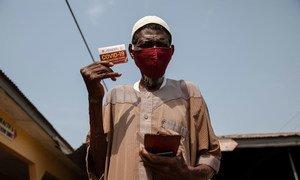 在加纳的卡索阿,一名76岁的老人在接种新冠疫苗后展示了他的疫苗接种卡。