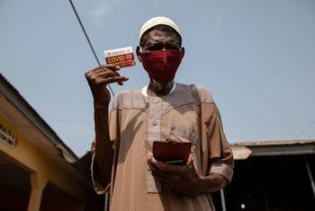 घाना के कसोआ में, कोविड-19 वैक्सीन का टीका लगवाने के बाद, एक 76 वर्षीय बुज़ुर्ग, अपना प्रमाण-पत्र दिखाते हुए.