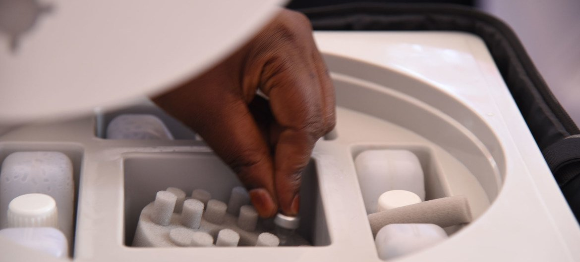 A health worker selects a vial of AstraZeneca COVID-19 vaccine from a cold box in Uganda.