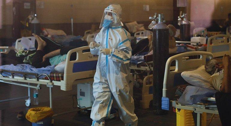 عامل صحي يعتني بالمرضى في قاعة تم تحويلها مؤقتا إلى جناح طوارئ كوفيد-19 في نيودلهي بالهند.
