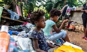 Family sits in the rubble of the house they lost in a 7.2 magnitude earthquake in Haiti.