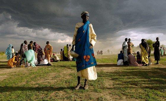 Idosa que vive como deslocada interna no Sudão se prepara para receber sua porção de ajuda alimentar emergencial.