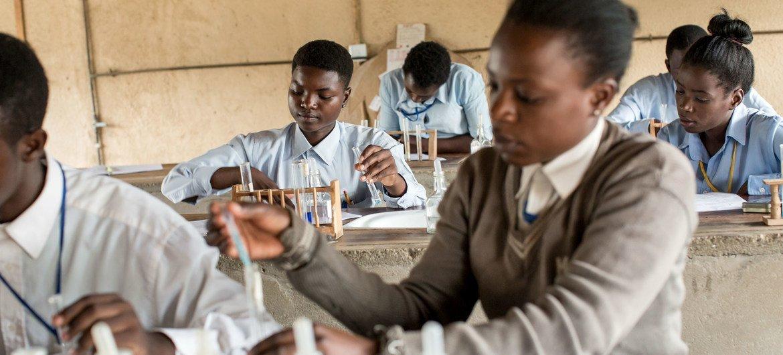 Menina na Zâmbia fazendo experiência química na escola